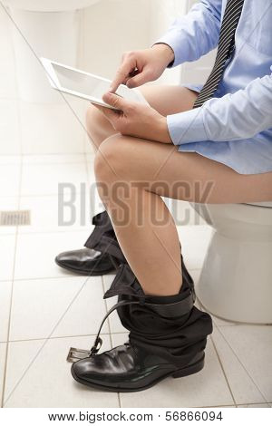 Man Using A Tablet Pc While Sitting On The Toilet.