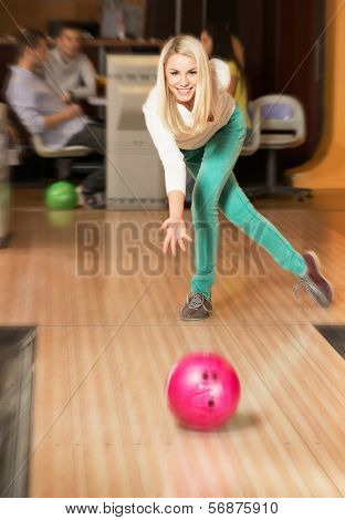 Young smiling blond woman throwing ball in a bowling club