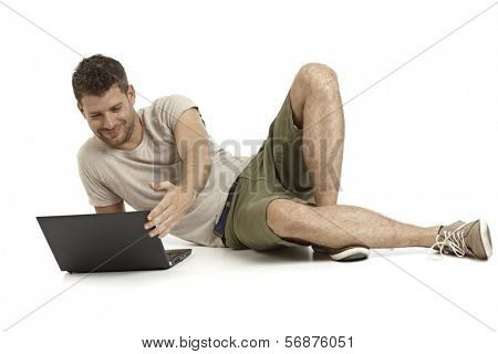Casual young man using laptop computer, lying on side, smiling.