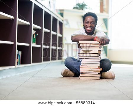 Full length portrait of happy African American student leaning on stacked books while sitting on floor at library