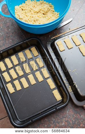 Raw Cookie Dough Being Cut And Packed Onto Baking Tray