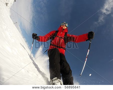 Skier performs a high speed turn on a ski slope. From the ski tip point of view. Sunny winter day. Concepts: vacation, speed, fun.