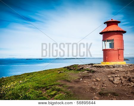 Little red lighthouse situated at the top of a cape over a sunny seascape. Related concept: navigation, help, aid, guide. Sykkisholmur, Iceland, Europe.