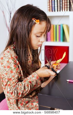 Little girl cutting a house on a red paper