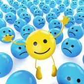 stock photo of smiley face  - A yellow smiley happy jumping among many sad blue others as concept for unique optimistic hapiness - JPG