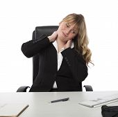 picture of stiff  - Pretty young female office worker with a stiff neck stretching and grimacing as she sits at her desk - JPG