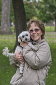 foto of maltipoo  - Adult Woman With Her Maltipoo Puppy At The Park - JPG