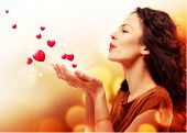stock photo of emotion  - Beauty Young Woman Blowing Hearts from her Hands - JPG