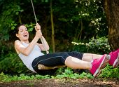 stock photo of seesaw  - Young woman swinging on seesaw outdoor in nature - JPG