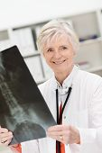 stock photo of roentgen  - Smiling female physician or radiologist checking a pelvic x - JPG