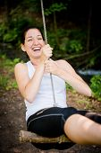 image of seesaw  - Young woman swinging on seesaw outdoor in nature - JPG