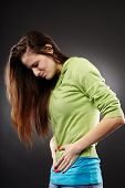 stock photo of colitis  - Studio shot of a young woman having a severe abdominal pain over grey background - JPG