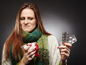 stock photo of blisters  - Studio shot of a woman holding a cup of hot tea and expressing disgust to some blister packed tablets she is holding over gray background - JPG