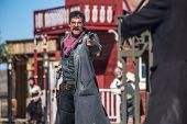 stock photo of outlaw  - A Sheriff Duels Bandit in the Middle of Town - JPG