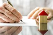 stock photo of deed  - Conceptual image of a man signing a mortgage or insurance contract or the deed of sale when buying a new house or selling his existing one with a small wooden model of a house alongside