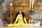 picture of ski boots  - Happy woman with skis and ski boots sitting near wooden wall in snowflakes - JPG