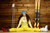 stock photo of ski boots  - Happy woman with skis and ski boots sitting near wooden wall - JPG