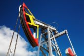 pic of nonrenewable  - Oil pump jack against blue sky background - JPG