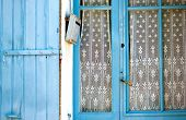 stock photo of lace-curtain  - Blue wooden shutter and door with lace curtain and a letter box in France - JPG