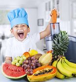 stock photo of juicer  - Happy little chef is making healthy fruit juice at home - JPG
