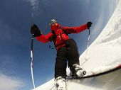Skier performs a high speed turn on a ski slope. From the ski tip point of view. Sunny winter day. C