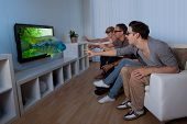 stock photo of realism  - Conceptual image of a family watching 3D television and stretching out their hands as though to touch the image on the screen - JPG