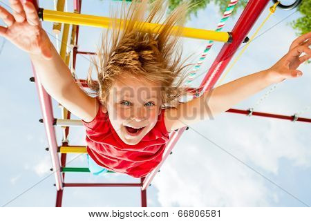 Little girl having fun playing on monkey bars