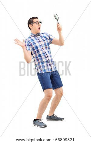 Full length portrait of an excited man looking through magnifier isolated on white background