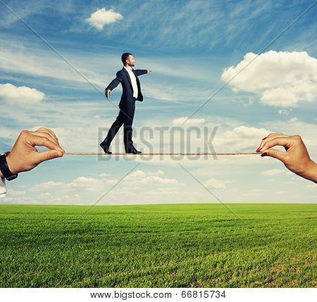 assured businessman tight rope walking outdoors.