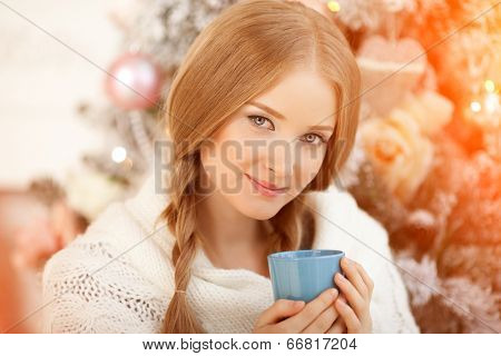 Beautiful young woman drinking tea at the Christmas tree. Beautiful girl celebrates Christmas with a cup of cocoa.