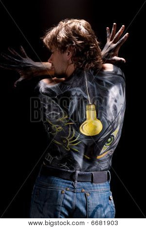 handsome man with body art on his back isolated on black