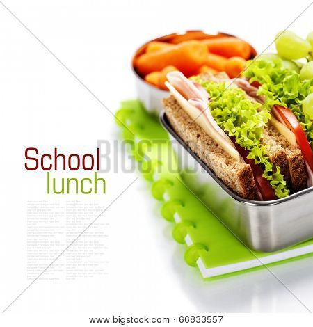 School lunch with a  ham sandwich, apple, grapes and textbooks