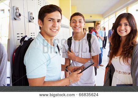 High School Students Standing By Lockers With Mobile Phone