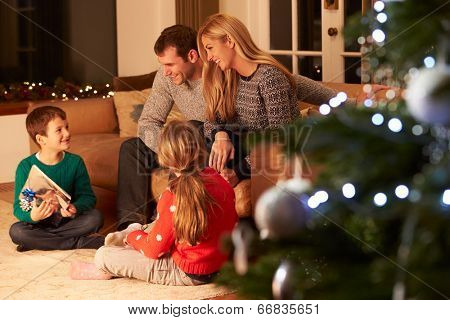 Family Exchanging Gifts By Christmas Tree