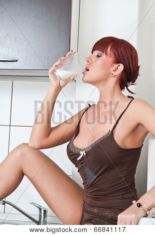 Attractive sexy woman in lingerie drinking milk in kitchen. Portrait of sensual girl