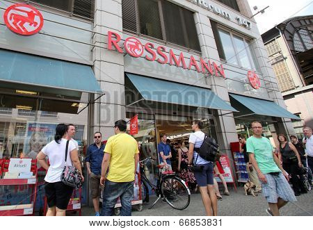 BERLIN, GERMANY - JUNE 11, 2014: Pedestrians walk past a Rossmann drugstore in  Berlin, Germany, on Saturday, June 11, 2014.  Dirk Rossmann GmbH is Germany's third largest drugstore chain.