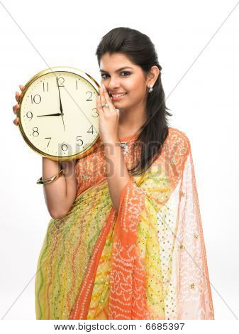 Asian woman holding big clock.