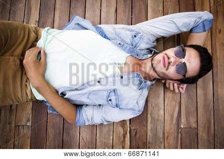 Young man lying on a wooden floor