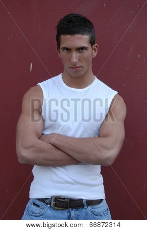 Young sexy man wearing a white tank top in front of a brown background