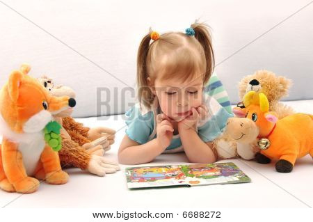 Little girl looking at pictures in the book.