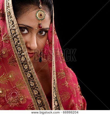 Portrait of beautiful mystery young Indian woman covering her face by headscarf, looking at camera, copy space at side, isolated on black background.