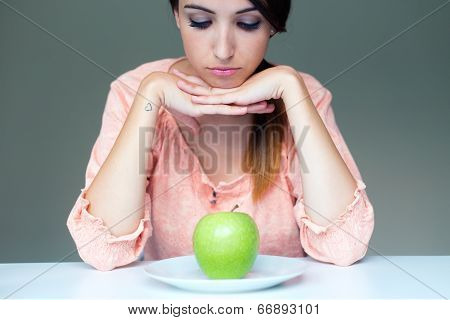 Upset Brunette Woman With Green Apple On A Plate