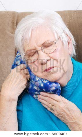Mujer Senior con hierba medicinal caliente Pack