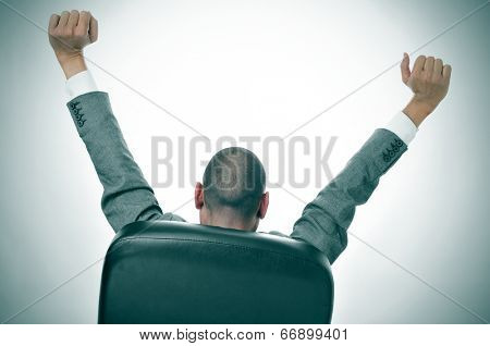 a businessman stretching in the chair of his office