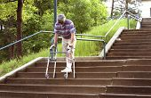 image of descending  - a mature man using a wheeled walker to descend a flight of steep stairs - JPG