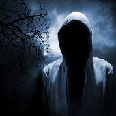 image of hooded sweatshirt  - Dangerous man hiding under the hood in the dark night forest - JPG
