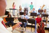 stock photo of clarinet  - Pupils Playing Musical Instruments In School Orchestra - JPG