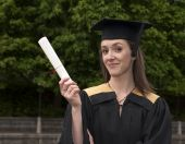 stock photo of convocation  - Young woman shows off certificate on graduation day - JPG