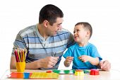 stock photo of molding clay  - Father and child play with clay together - JPG