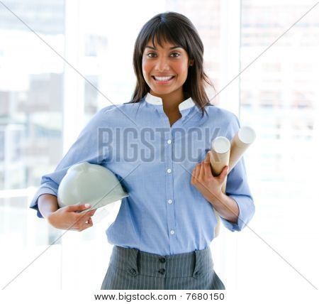 Smiling Female Architect Holding A Hardhat And Blueprints Standing